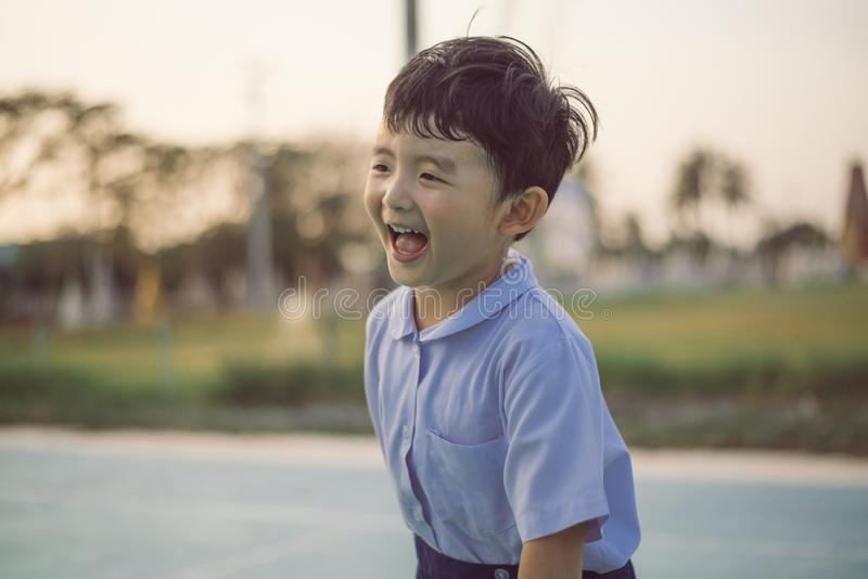 Outdoor portrait of a happy Asian student kid in school uniform smiling stock photo