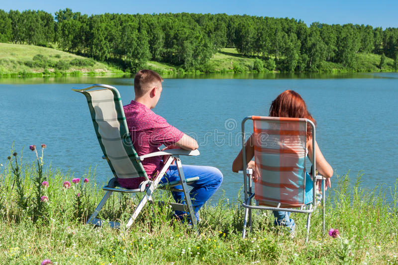 Outdoor portrait of happy couples at the lake, sitting in a chair stock image