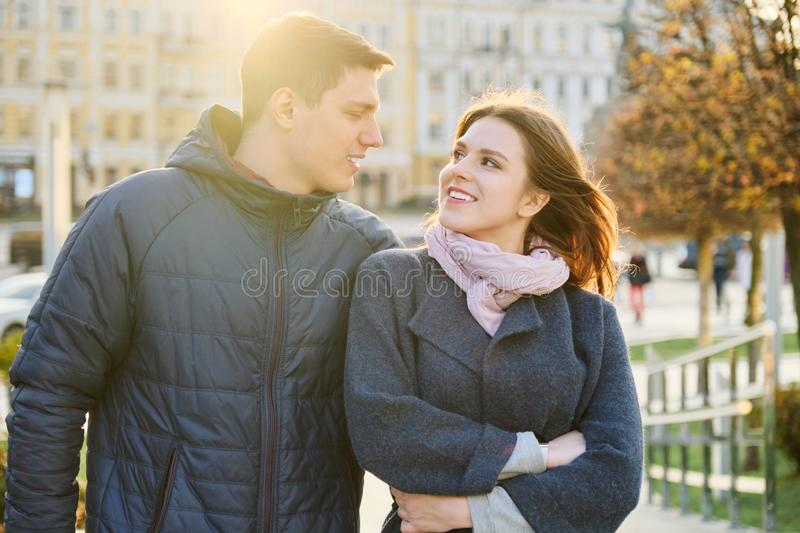 Outdoor portrait of happy embracing couple, handsome man and woman walking, background evening city royalty free stock images