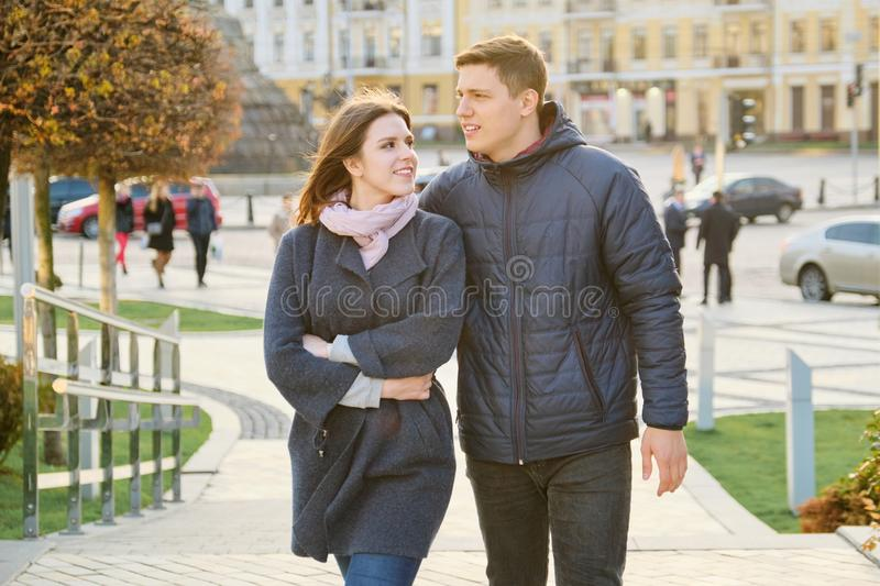 Outdoor portrait of happy embracing couple, handsome man and woman walking, background evening city royalty free stock image