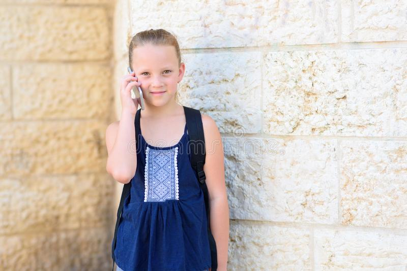 Outdoor portrait of happy girl 8-9 year old talking on phone. stock photo