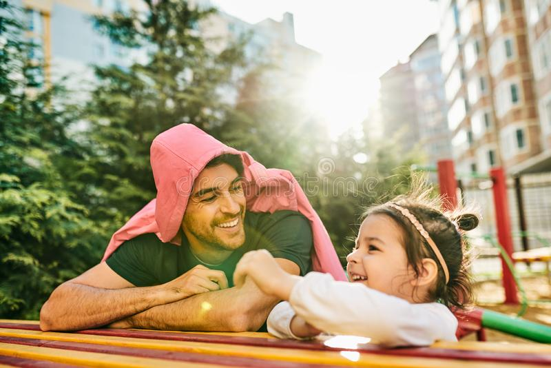 Outdoor portrait of happy kid, cute little girl smiling and playing with her daddy. Handsome dad and toddler child having fun and stock images