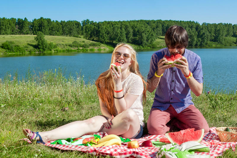Outdoor portrait of happy loving couple at the lake, which is eating watermelon stock photography
