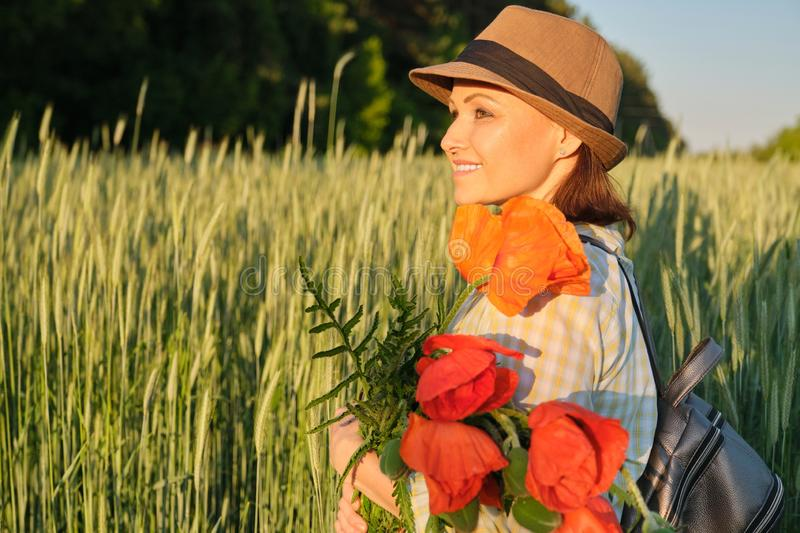 Outdoor portrait of happy mature woman with bouquets of red poppies flowers. Background summer field of wheat on sunset, golden hour royalty free stock photo