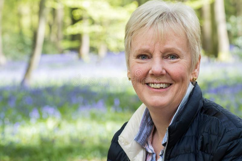Outdoor Portrait Of Happy Senior Woman In Bluebell Wood royalty free stock photo