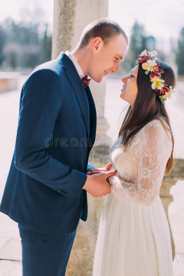 Outdoor portrait of happy sensual wedding pair embracing. Beautiful young bride going to kiss with handsome groom stock images