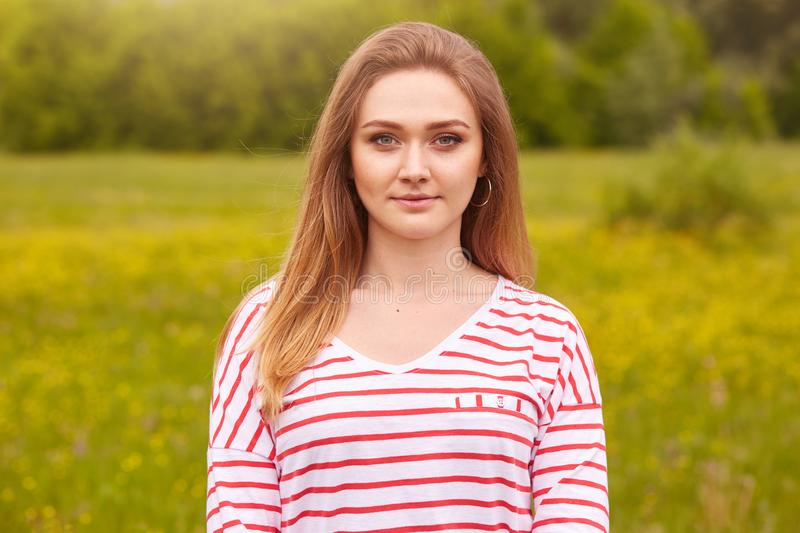 Outdoor portrait of happy smiling girl with long straight hair in white shirt with red stripes posing in summer meadow, has calm stock photography
