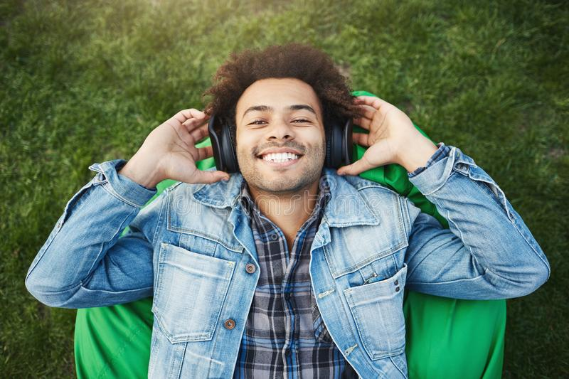Outdoor portrait of happy upbeat dark-skinned male with bristle and afro haircut lying on bean bag chair or grass. Smiling broadly while listening music via royalty free stock photo