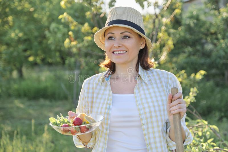 Outdoor portrait of happy woman 40 years old, female in garden in straw hat with plate of strawberries mint lemon stock photos