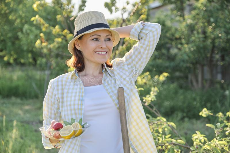Outdoor portrait of happy woman 40 years old, female in garden in straw hat with plate of strawberries mint lemon royalty free stock photo