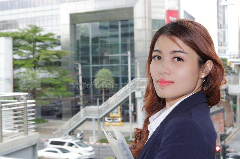 Outdoor portrait of happy young Asian business woman looking at camera in the city background. stock photo