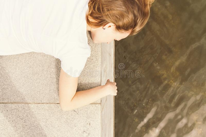 Outdoor portrait of happy young woman on city promenade. Girl lies on granite embankment royalty free stock photos