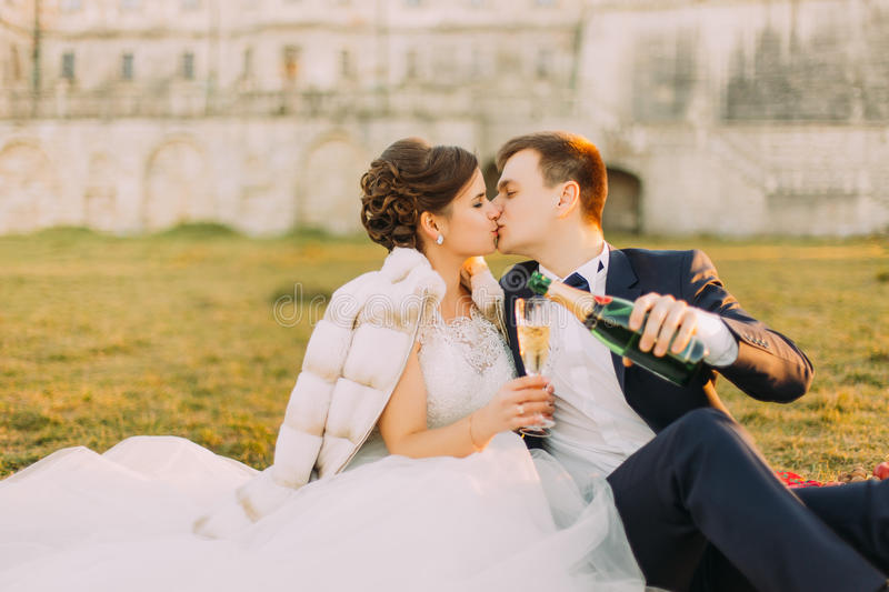 The outdoor portrait of the kissing newlyweds during their picnic at the background of the old-fashioned castle. royalty free stock photography