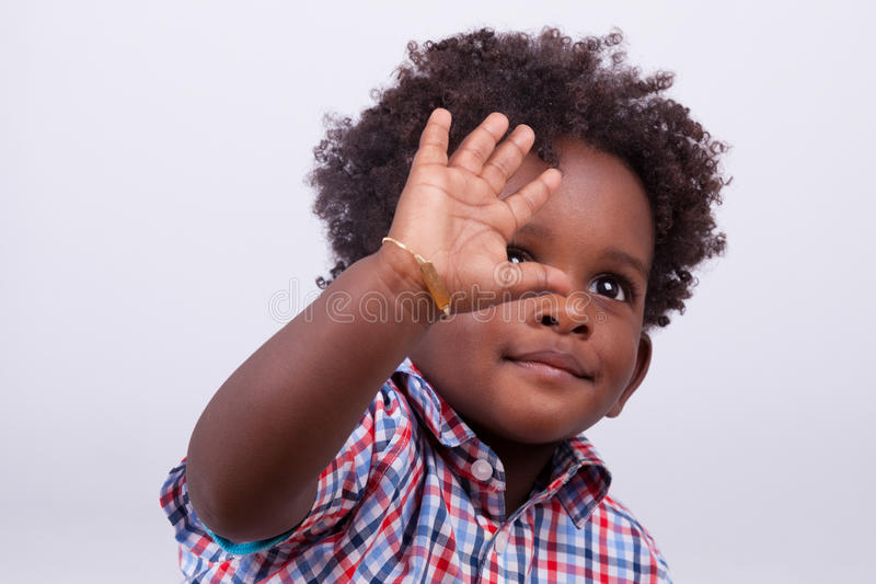 Outdoor portrait of a little african american boy - Black - children - people. Outdoor portrait of a little african american boy, isolated on grey background royalty free stock photo