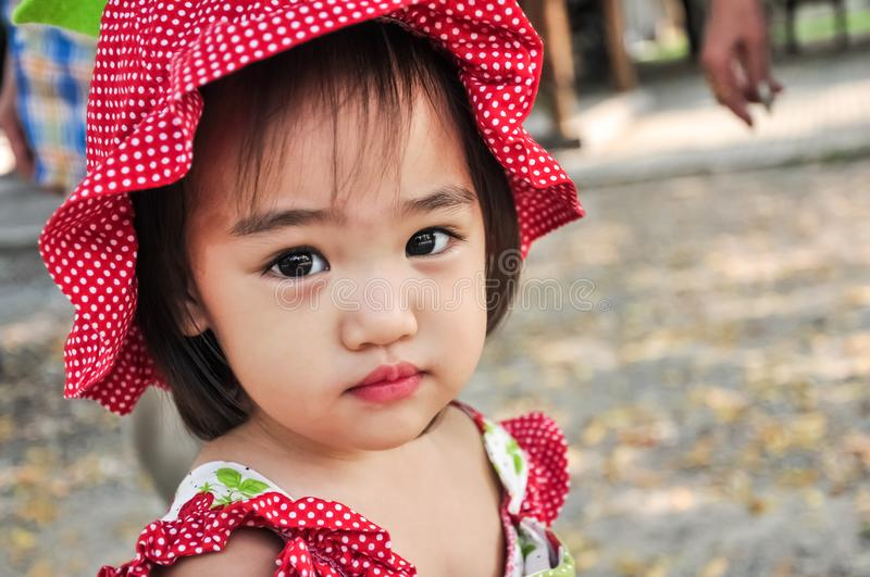 Outdoor Portrait of Little asian girl Wearing red hat. royalty free stock images