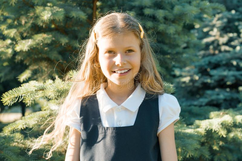 Outdoor portrait of a little beautiful smiling schoolgirl blonde with long curly hair in school uniform royalty free stock photos