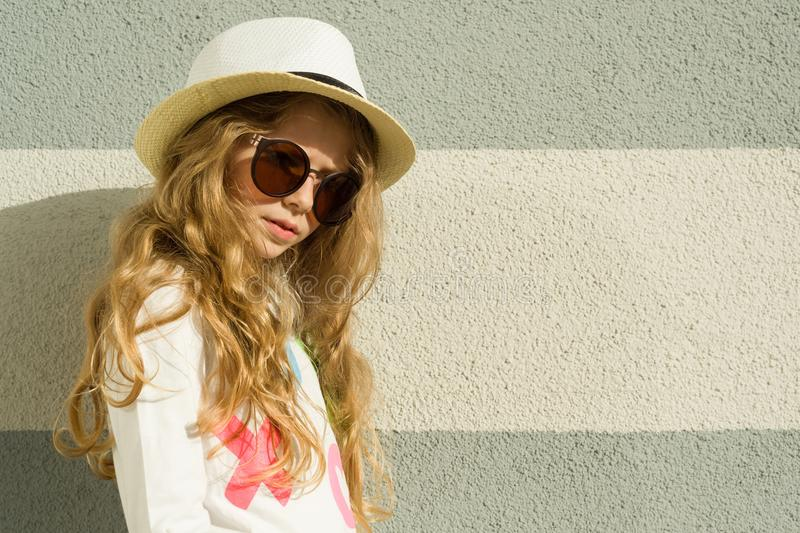 Outdoor portrait little blonde girl with long curly hair, sunglasses in straw hat. Gray textured wall background, copy space royalty free stock images