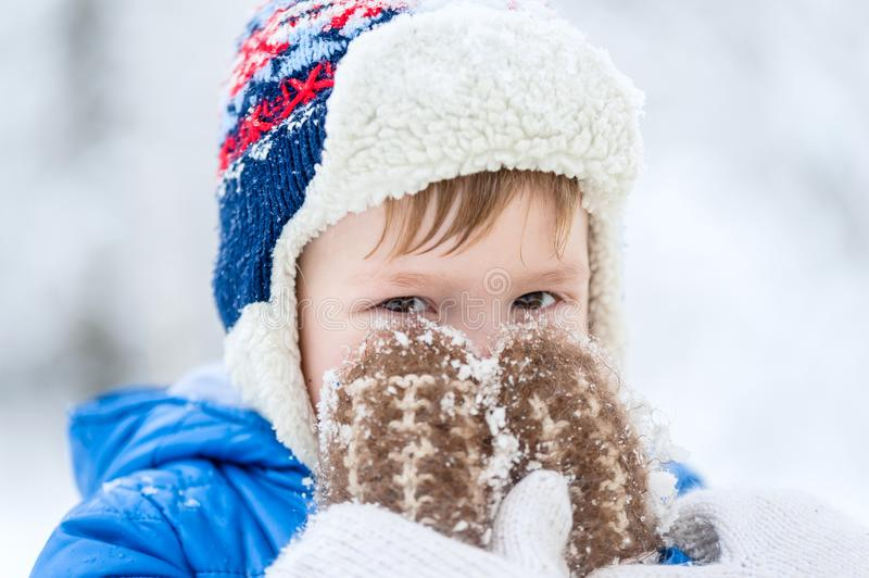 Outdoor portrait Little boy covered his face mittens. Visible only to the eyes royalty free stock photos