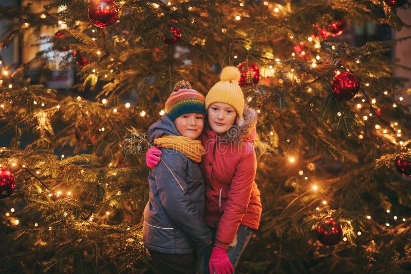Outdoor portrait of little children next to Christmas tree with lights stock photos