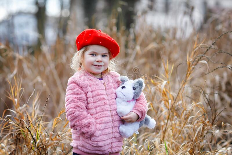 Outdoor portrait of little cute toddler girl in pink coat and red fashion hat barret playing with soft plush dog toy stock images