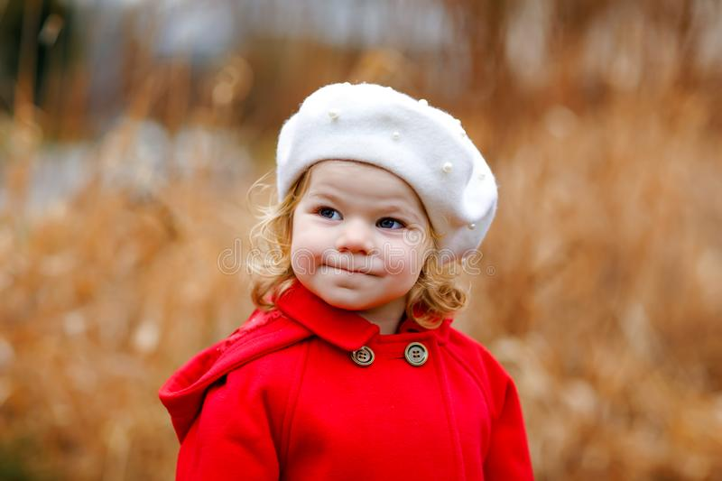 Outdoor portrait of little cute toddler girl in red coat and white fashion hat barret. Healthy happy baby child walking royalty free stock images