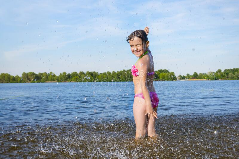 An outdoor portrait of a little girl playing on the beach with splashing water.  Summer holidays and healthy lifestyle concept stock photos