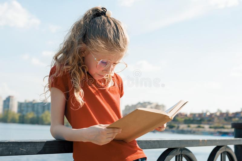 Outdoor portrait of little schoolgirl with book, girl child 7, 8 years old with glasses reading textbook.  royalty free stock photos