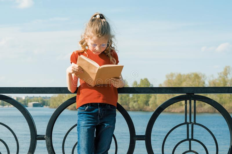Outdoor portrait of little schoolgirl with book, girl child 7, 8 years old with glasses reading textbook stock images