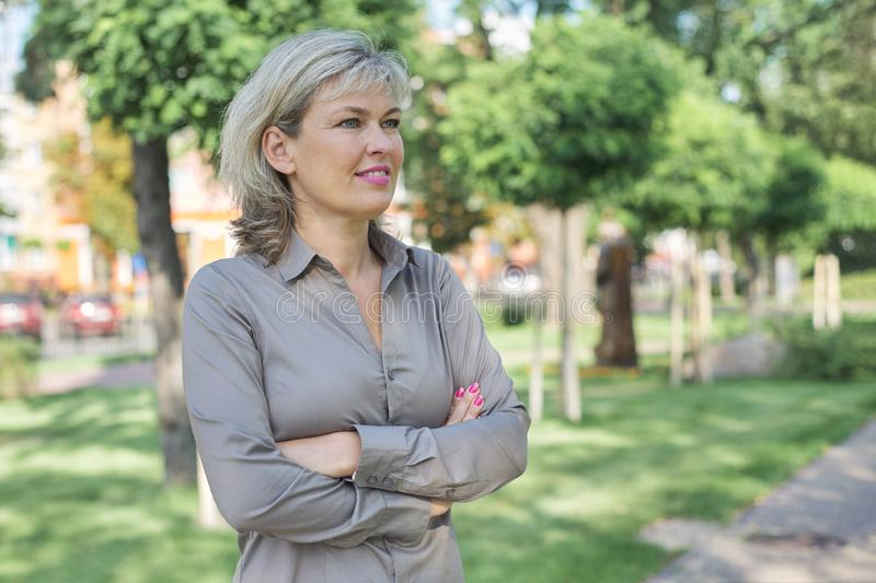 Outdoor portrait of mature businesswoman on city street royalty free stock image