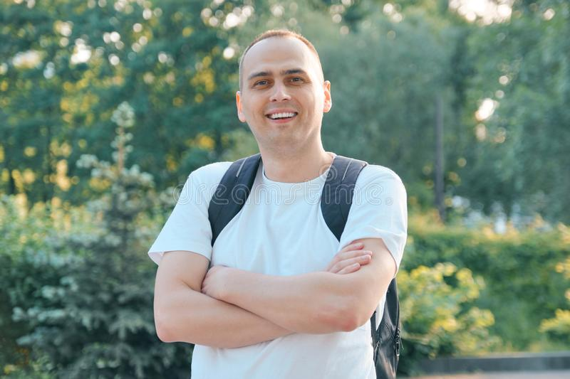 Outdoor portrait of mature smiling positive man. Confident male in white T-shirt with backpack with folded hands looking at the stock photos