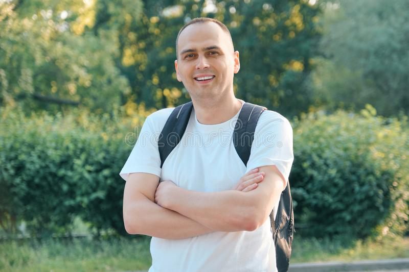 Outdoor portrait of mature smiling positive man. Confident male in white T-shirt with backpack with folded hands looking at the royalty free stock photo