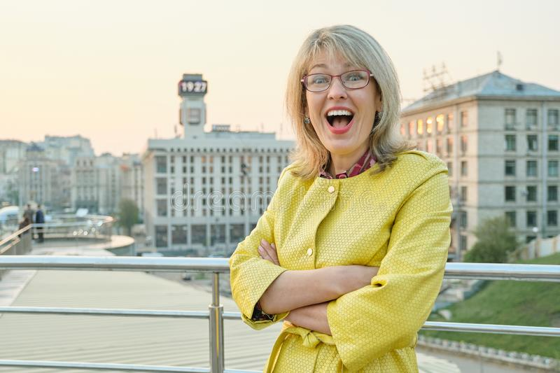 Outdoor portrait of mature smiling woman with glasses, yellow jacket. Female 40,45 years old, spring park background, copy space.  stock image