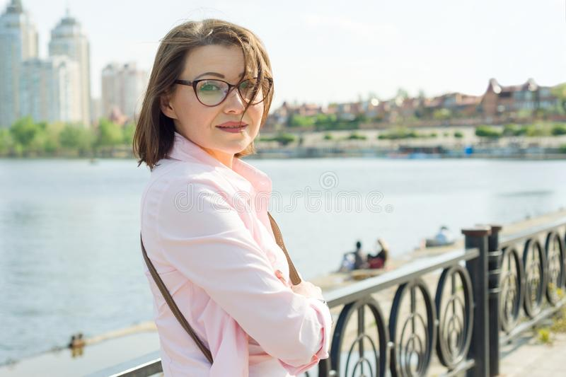 Outdoor portrait middle aged woman. Background street, city, river. royalty free stock photo
