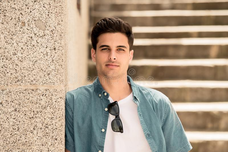 Outdoor portrait of modern attractive young man in the city. Urban background royalty free stock photos
