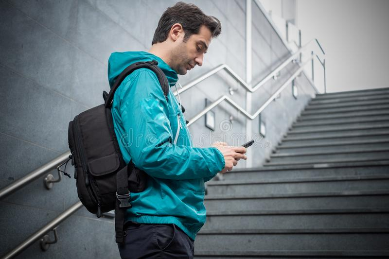 Casual urban male using smartphone on stairs. Outdoor portrait of modern young man with mobile phone royalty free stock image