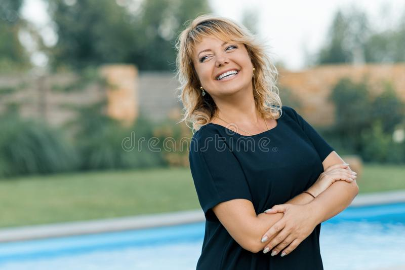 Outdoor portrait of positive confident mature woman. Smiling female blonde with arms crossed, background of pool, private royalty free stock image