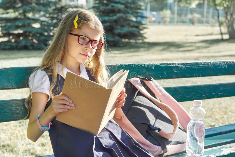 Outdoor portrait of pretty little girl in school uniform glasses, with backpack bottle of water, reading book royalty free stock photos