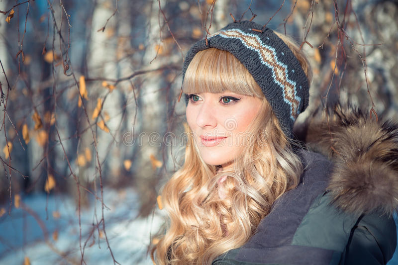 Outdoor portrait of pretty plus size model having fun. Attractive young woman wearing purple warm coat, white wool knitted cap and scarf in cold winter weather stock photos