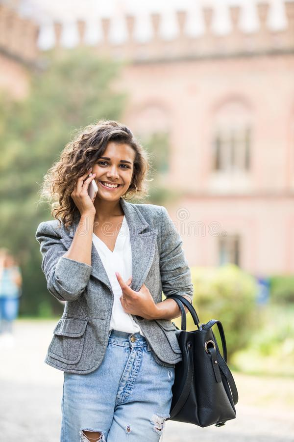 Outdoor portrait of pretty student girl talking on the phone royalty free stock images
