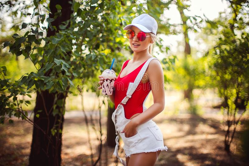 Outdoor portrait of pretty stylish fashion girl having fun drinking milkshake. royalty free stock images