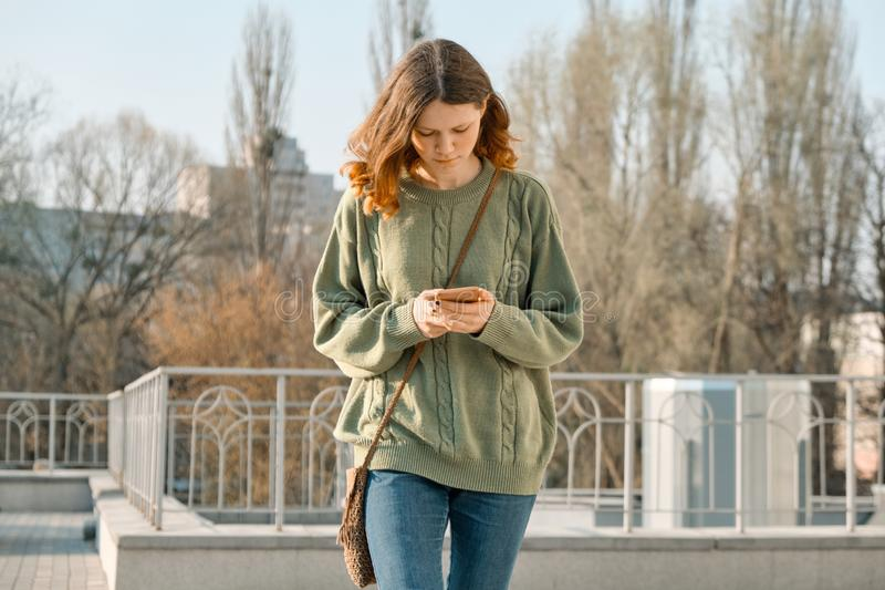 Outdoor portrait of pretty teen girl walking and texting on mobile phone, spring sunny day background stock images