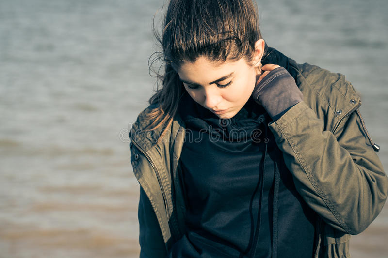 Outdoor portrait of a pretty teenage girl. Wearing khaki parka and walking on the beach stock photos