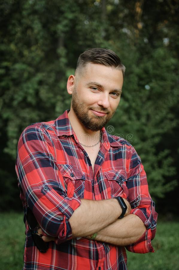 Outdoor portrait of relaxed handsome young man with beard in the park on green trees background. Hipster style concept. royalty free stock photography