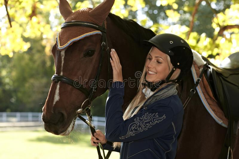 Outdoor portrait of rider and horse. Outdoor portrait of female rider caressing horse royalty free stock photography