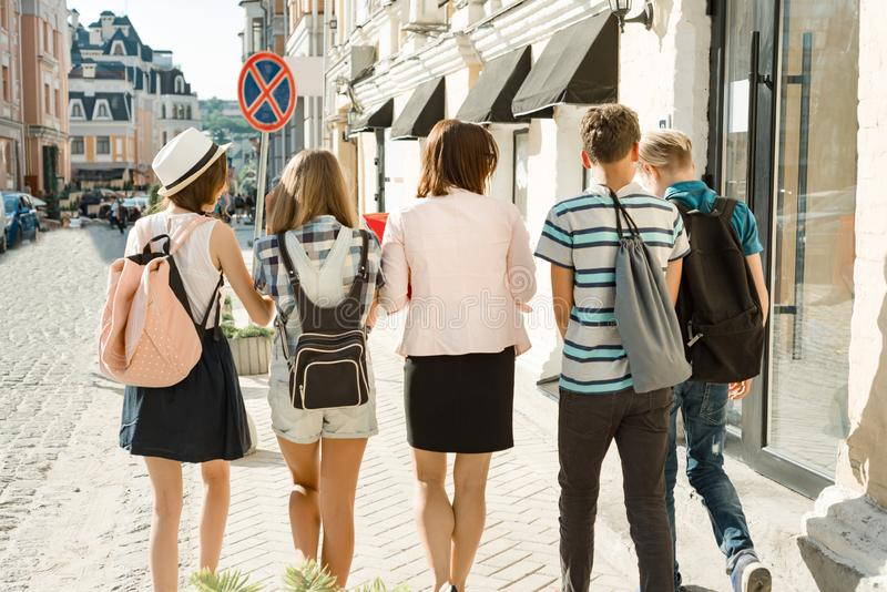 Outdoor portrait of school teacher and group of teenagers high school students. Children walking with teacher, view from the back royalty free stock image