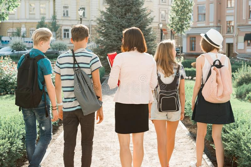 Outdoor portrait of school teacher and group of teenagers high school students. Children walking with teacher, view from the back stock photography