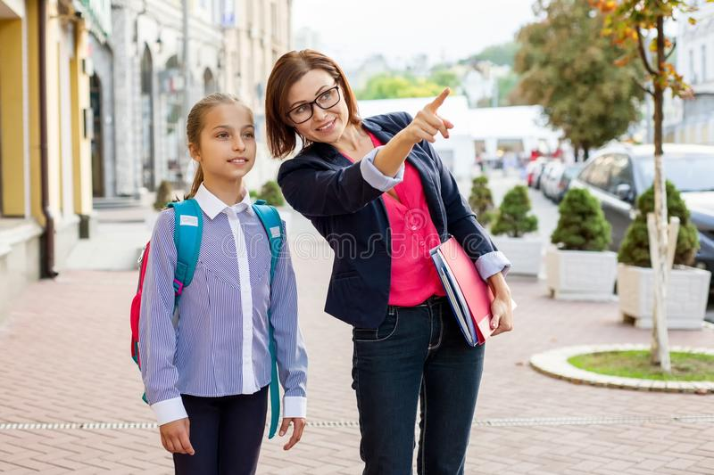 Outdoor portrait of schoolgirl and teacher. royalty free stock photography