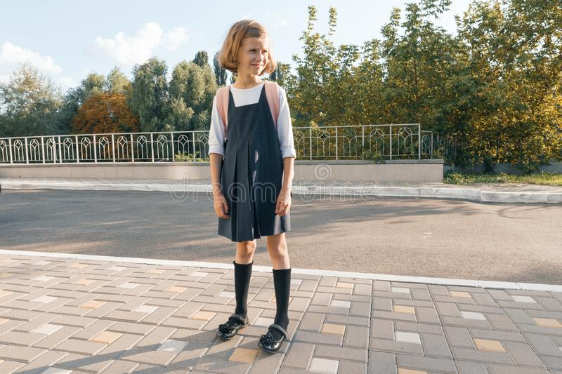Outdoor portrait of a small student, girl with glasses, uniform with backpack. School, education, knowledge and children stock photos