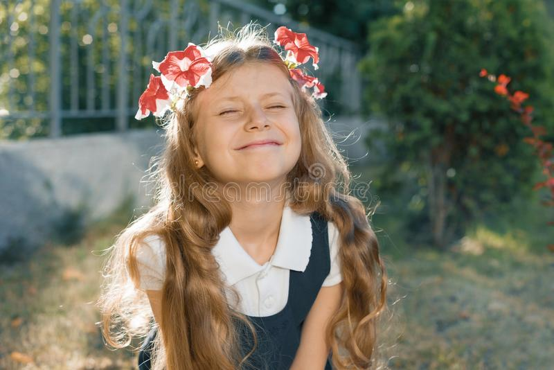 Outdoor portrait of smiling child girl in wreath of pink flowers with eyes closed, girl with blond long wavy hair stock photos