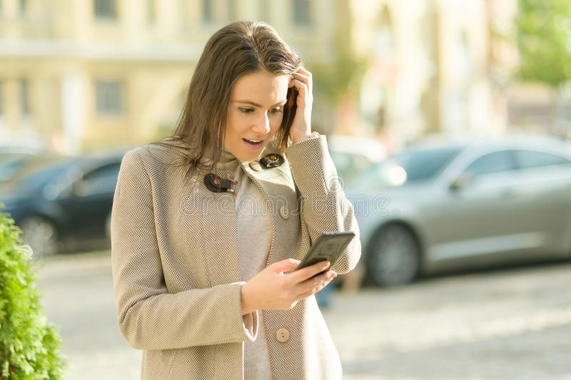 Outdoor portrait of a smiling happy young woman with smartphone, city street background, autumn sunny day. Girl reacts emotionally royalty free stock photos